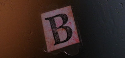 The letter B printed on paper, found under the fingernail of one of the bodies.