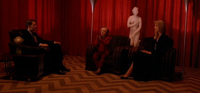 A full shot of the red room, complete with striped zig-zag floor, red curtains and three guests.