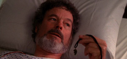 Dr. Jacoby lies in a hospital bed while holding Laura's necklace.