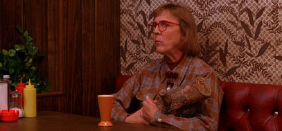 Twin Peak's log lady sits at a table in the diner.