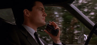 Dale speaks into his dictaphone while driving into Twin Peaks.
