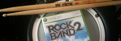 Rock Band 2 game box resting on a drum pad next to a pair of drum sticks.