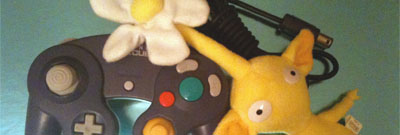 A yellow Pikmin cuddles up to a purple Gamecube controller.