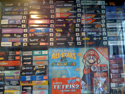Stacks upon stacks of boxed N64 games in a glass cabinet.