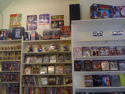 DVDs and collectibles on shop shelves with console boxes on top.