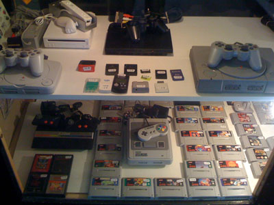 Various retro consoles under the glass counter.