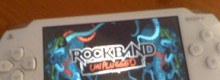 The Rock Band: Unplugged title screen on a white PSP.