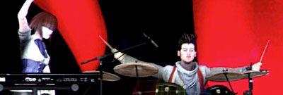 A keyboardist and drummer from Rock Band 3, against an angry red background.