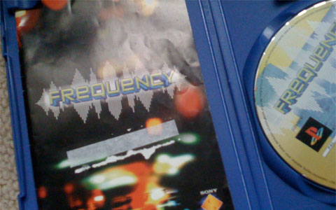 The inside of the Frequency box, with the manual damaged by a sticker.