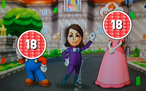 A Mario Kart winning picture, Peach and Mario's faces are covered by an 18 rating.